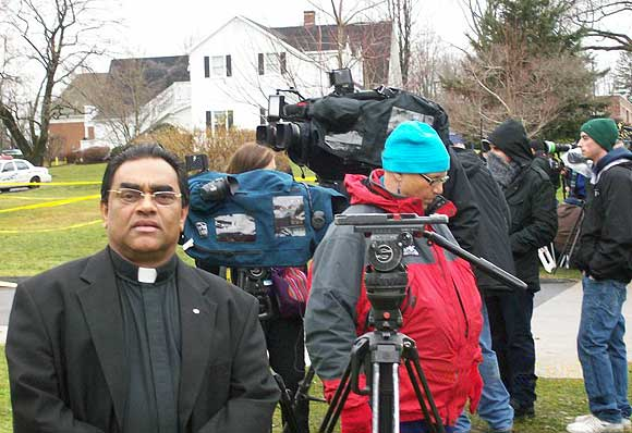 Reverend Dr Francis Luke Nambiaparambil is seen along with the media crew outside the church