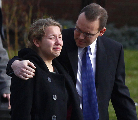 A man hugs a crying girl as they leave the funeral of Jessica Rekos at St Rose of Lima Church in Newtown, Connecticut