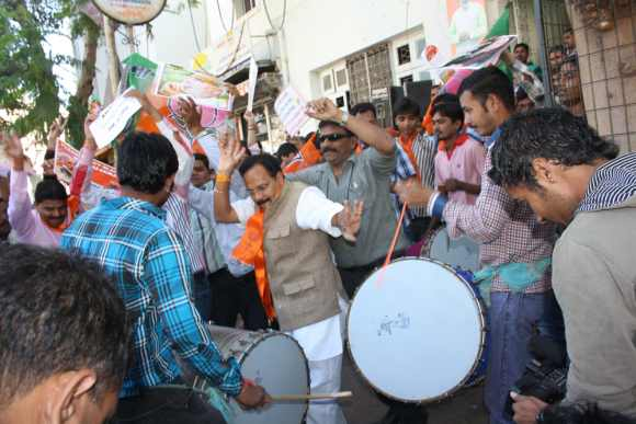 BJP workers dance outside the party headquarters in Khanpur as the news of Modi's victory from the Maninagar constituency comes in