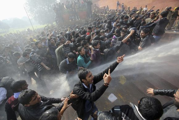 Demonstrators shout slogans as police use water cannons to disperse them at Raisina Hills during a protest rally in New Delhi