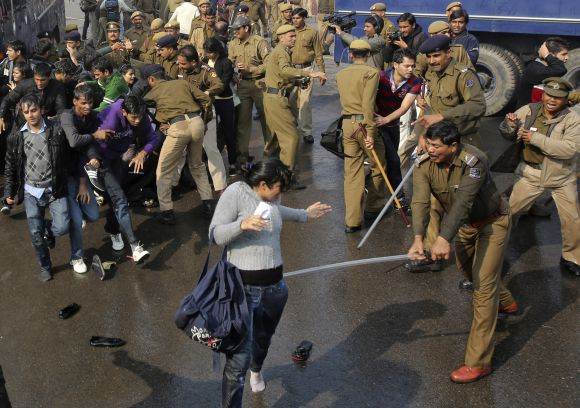 A policeman wields his baton against a female demonstrator at Raisina Hills in New Delhi