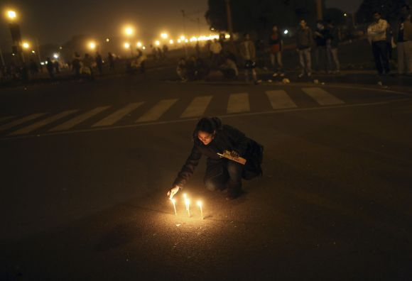 A demonstrator lights candles near the presidential palace during a protest rally in New Delhi