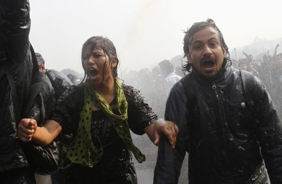 Demonstrators shout slogans as they are hit by police water cannon near the Rashtrapati Bhavan