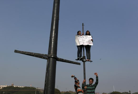 Demonstrators shout slogans and carry a placard while standing on lamp posts during a protest rally near the presidential palace in New Delhi