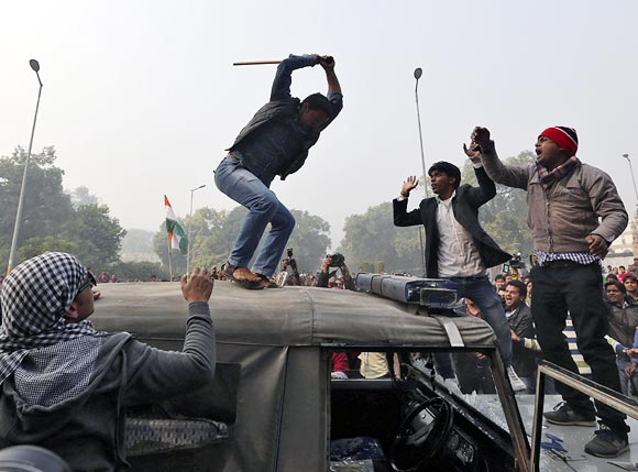 A demonstrator breaks the windshield of a police vehicle as others shout slogans in front of the India Gate