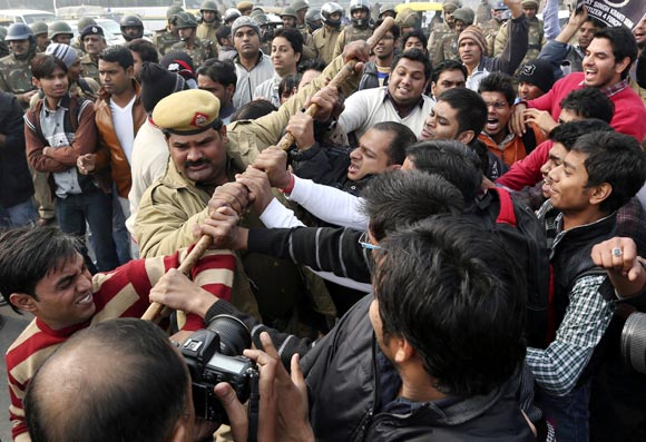 A policeman tries to stop demonstrators in front of the India Gate