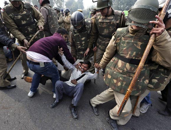 Police detain demonstrators in front of the India Gate during a protest in New Delhi