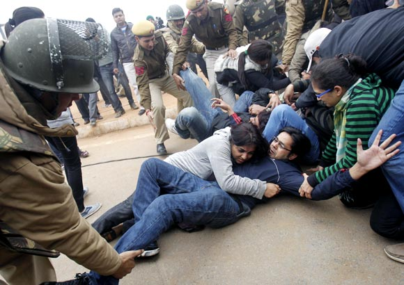 Demonstrators huddle as police try to detain them in front of the India Gate