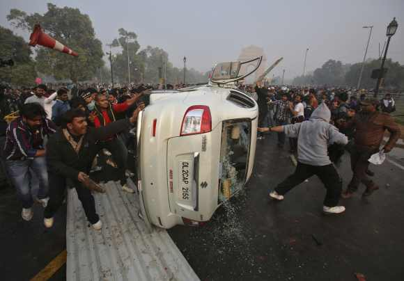 Demonstrators damage a government vehicle after they overturn it in front of the India Gate
