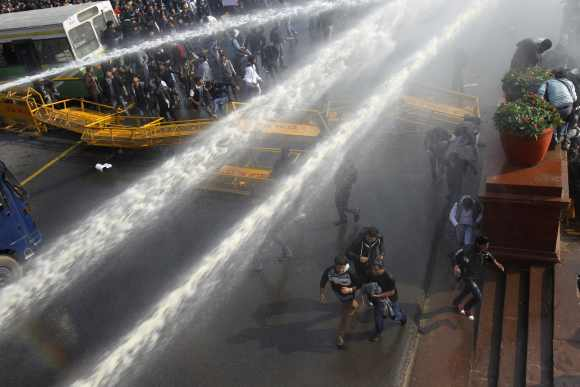Demonstrators are hit by police water cannons near the presidential palace during a protest rally in New Delhi