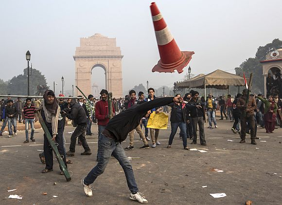 Protestors throw projectiles at Delhi police officers during the protest