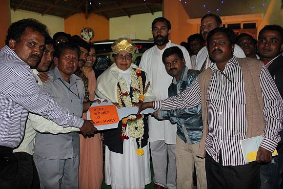Former patients of the Sumanhalli Society present the keys to the Tata Nano to Sister Mary on her 75th birthday
