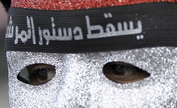 A protester against Egyptian President Mohamed Mursi wears a mask with the colours of Egypt's national flag and a headband at Tahrir Square in Cairo