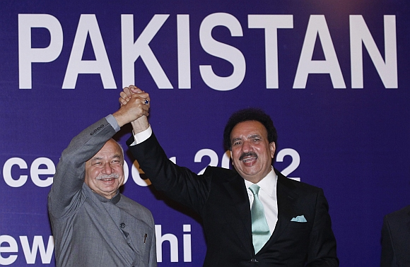 Pakistan's Interior Minister Rehman Malik and Indian Home Minister Sushil Kumar Shinde hold hands after the launch of a new visa agreement between India and Pakistan, in New Delhi