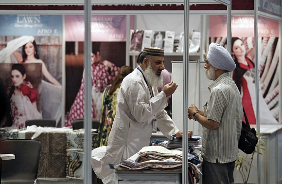 A Pakistan exhibitor speaks with a Sikh visitor at the Lifestyle Pakistan Exhibition in New Delhi