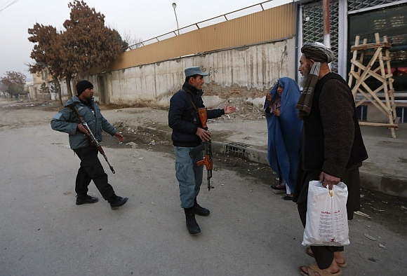 Afghan policemen stand guard near the site of a suicide attack that wounded Afghanistan's Intelligence chief Asadullah Khalid in Kabul