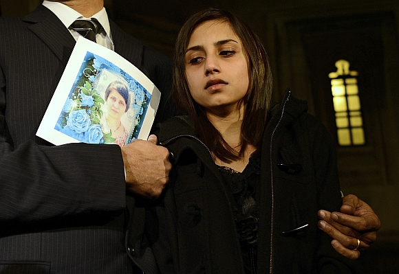 Lisha Barboza reacts as she stands with her father Ben while he holds a picture of his wife, nurse Jacintha Saldanha, as they leave the Houses of Parliament in London