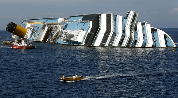 A boat sails past capsised cruise liner Costa Concordia near the harbour of Giglio Porto