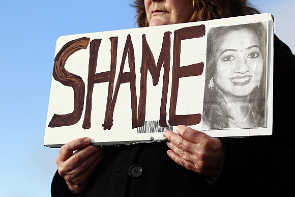Mary Phelan holds a picture of Savita Halappanavar in protest outside University Hospital Galway in Galway, Ireland