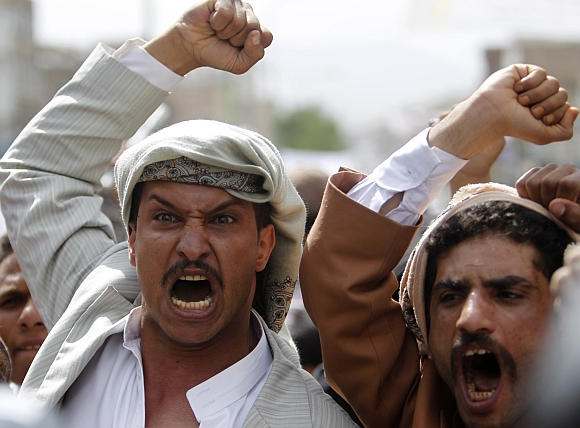 Protesters shout slogans during a protest on a road leading to the US embassy in Sanaa