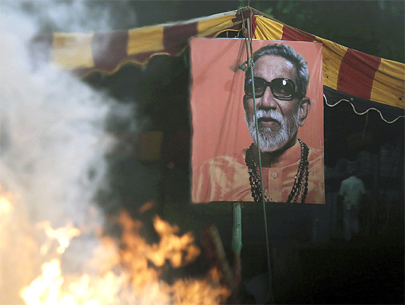A portrait of right-wing Hindu nationalist politician Bal Thackeray is pictured through the heat haze rising from his cremation pyre during his funeral at Shivaji Park in Mumbai