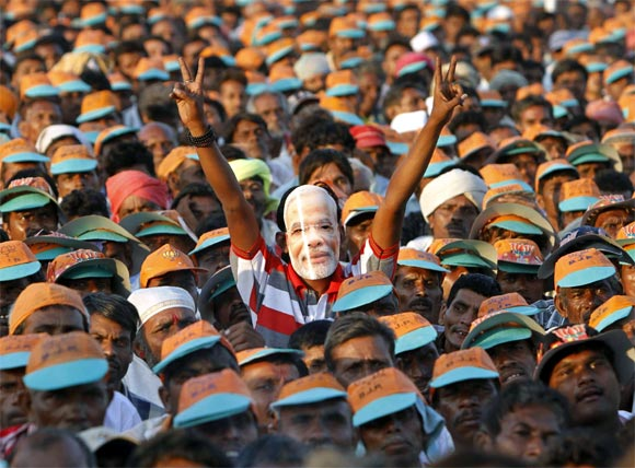 A supporter of Gujarat's Chief Minister Narendra Modi wears a mask during an election campaign rally at Pavagadh in Gujarat