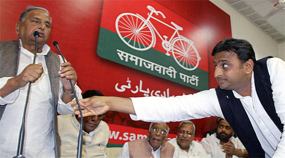 Uttar Pradesh Chief Minister Akhilesh Yadav adjusts the microphone for his father, the Samajwadi Party President Mulayam Singh Yadav, at the party headquarters in Lucknow