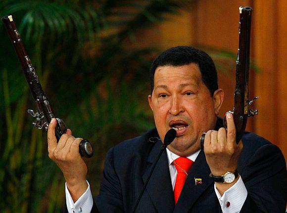 Venezuelan President Hugo Chavez shows the pistols of independence hero Simon Bolivar during a ceremony to mark the his birthday in Caracas