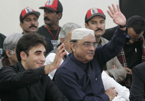Bilawal Bhutto Zardari (L), son of assassinated former Pakistani prime minister Benazir Bhutto, and his father, Pakistan's President Asif Ali Zardari, wave to the crowd during the fifth anniversary of Benazir Bhutto's death, at the Bhutto family mausoleum in Garhi Khuda Bakhsh, near Larkana