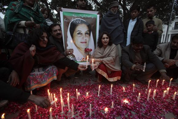 Pakistan Peoples Party supporters light candles beside a poster of Pakistan's former prime minister Benazir Bhutto during her death anniversary in Lahore
