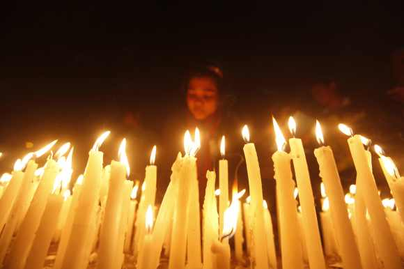 A girl lights candles during a candlelight vigil in Kolkata