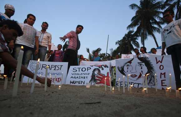 Demonstrators light candles and place placards in the sand during a protest rally in solidarity with a rape victim from New Delhi in Mumbai