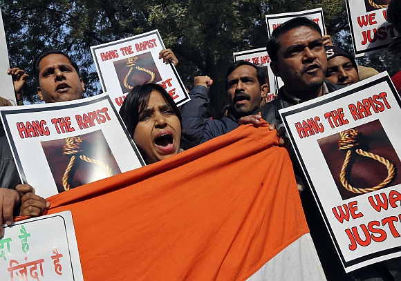 People shout slogans and hold placards during a protest in New Delhi