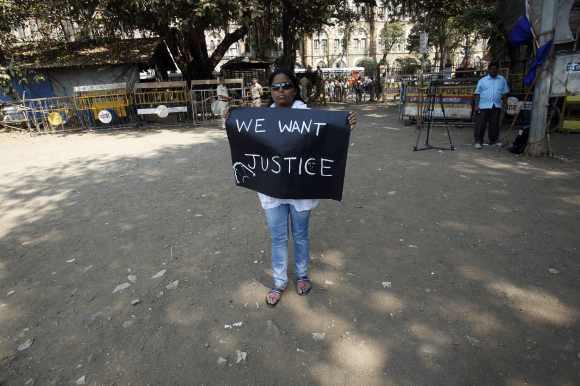 A protester holds a sign as she takes part in a demonstration to mourn the death of a rape victim, who was assaulted in New Delhi, in Mumbai