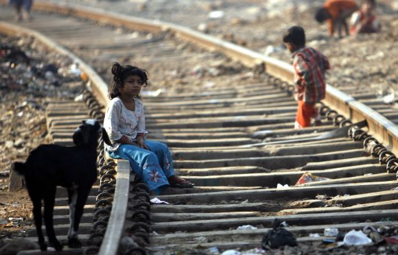 A girl sits on a rail track in a slum in Mumbai