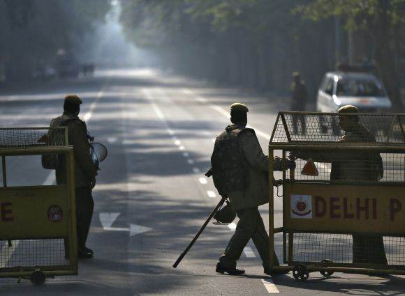 A police officer pulls a barricade to close a road leading to India Gate in New Delhi