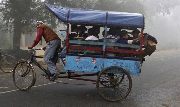 A man pedals his trishaw carrying school children in Allahabad
