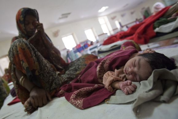 A woman sits on a bed along with her new born baby at a district hospital in Madhya Pradesh.
