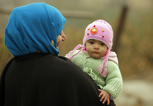 A woman walks while carrying her eight-month-old baby girl on a cold morning in Srinagar