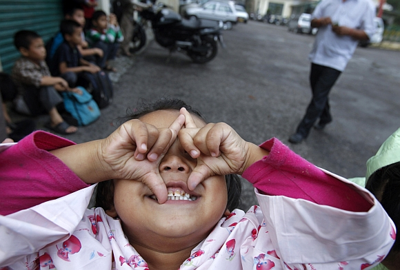 A girl playfully reacts to being photographed while waiting for a school bus in Dharamsala