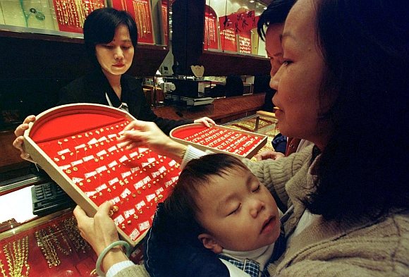 A woman carrying her sleeping baby picks up a gold earring at a jewellry shop in Hong Kong