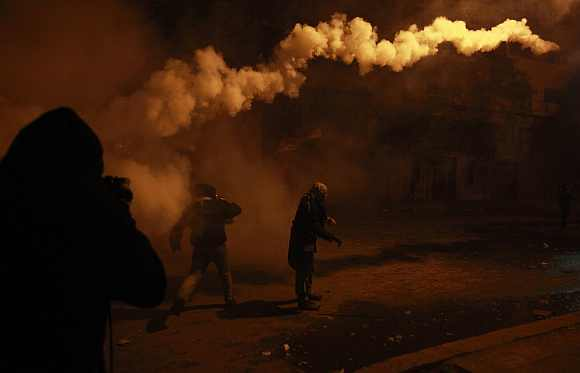 A protester returns a gas canister during clashes with security forces in Cairo on February 2