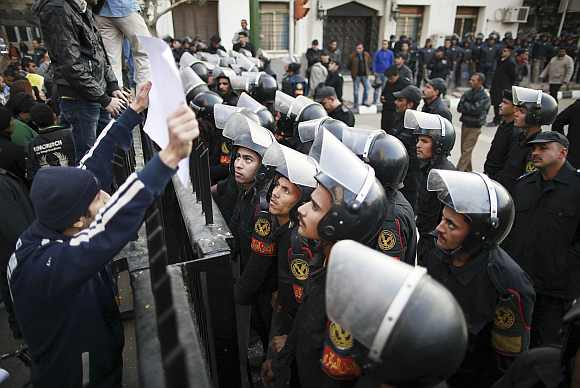 Riot police look at a banner held by a protester during a protest condemning the killings that happened on Wednesday at Port Said stadium