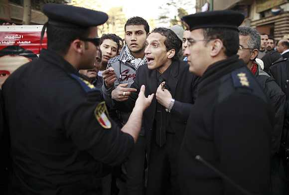 A demonstrator talks with police officials during a protest condemning the deaths that happened on Wednesday at Port Said stadium