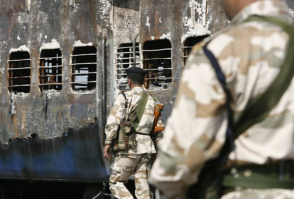 Rapid Action Force personnel stand guard besides a burnt carriage of a Samjhauta Express train in Deewana, near Panipat town, on February 19, 2007. Two bombs exploded aboard a train bound for Pakistan, sparking a fire that killed 68 passengers