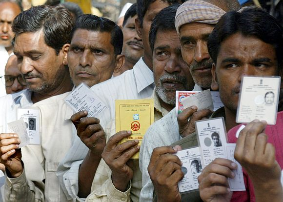 Voters display their election identity cards outside a polling booth in Shahjahanpur, Uttar Pradesh