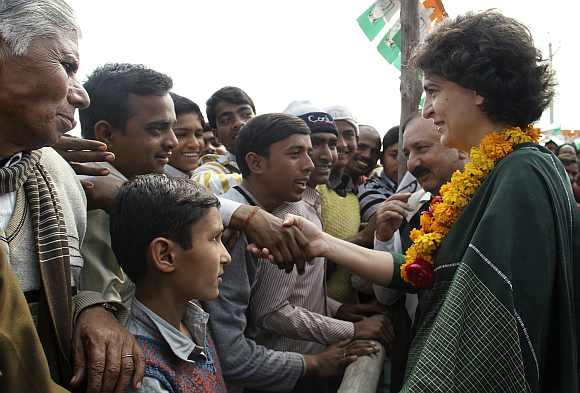Priyanka Gandhi shakes hands with a supporter of the party during an election campaign rally at Amethi