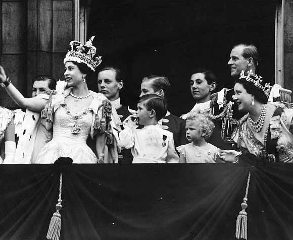 Queen Elizabeth II with (left to right) Charles, Prince of Wales, Anne the Princess Royal, Prince Philip the Duke of Edinburgh, and the Queen Elizabeth the Queen Mother watching an RAF fly-past from the balcony of Buckingham Palace as part of the Queen's Coronation ceremony on June 2, 1953