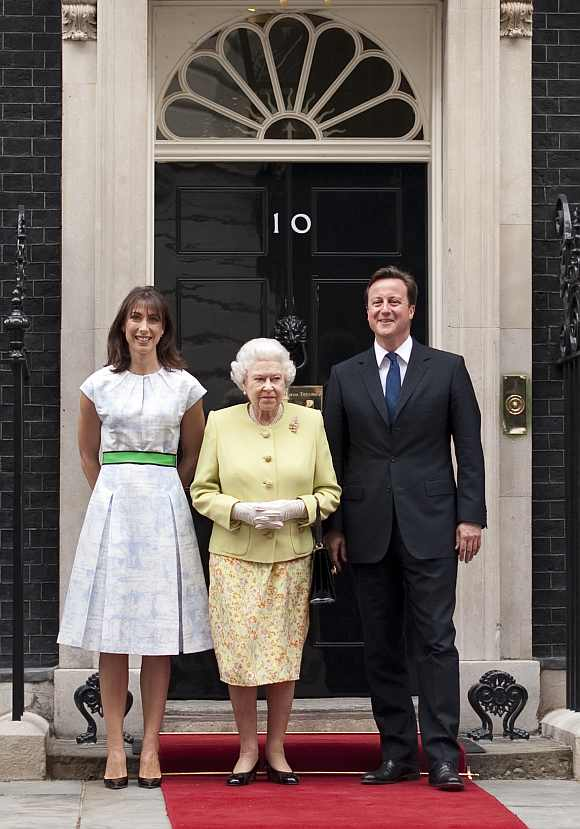 Britain's Queen Elizabeth poses with Prime Minister David Cameron and his wife Samantha before a lunch to celebrate Prince Philip's 90th birthday at number 10 Downing Street in London