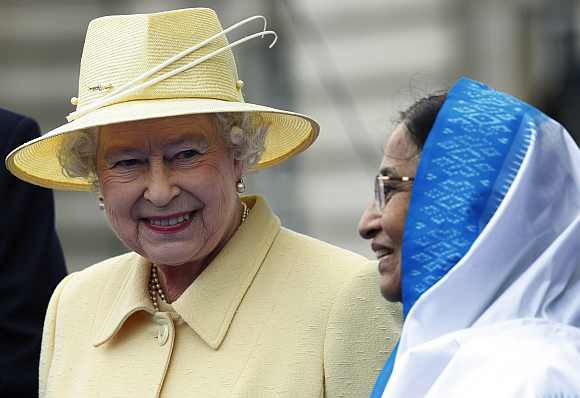 Queen Elizabeth II and President Pratibha Patil smile during a ceremonial baton handover to launch the Commonwealth Games